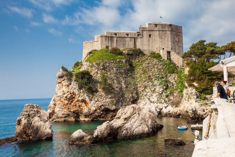 Acople dos turistas que olham o cais ocidental de Dubrovnik e o forte medieval Lovrijenac situado na parede ocidental da cidade fotografia de stock royalty free