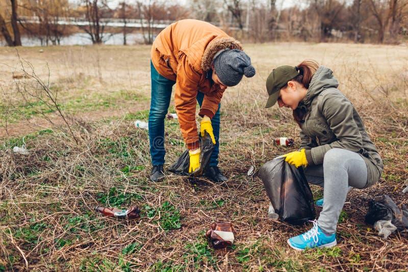 Acople dos voluntários que limpam o lixo no parque Da colheita lixo acima fora Conceito da ecologia e do ambiente imagem de stock royalty free
