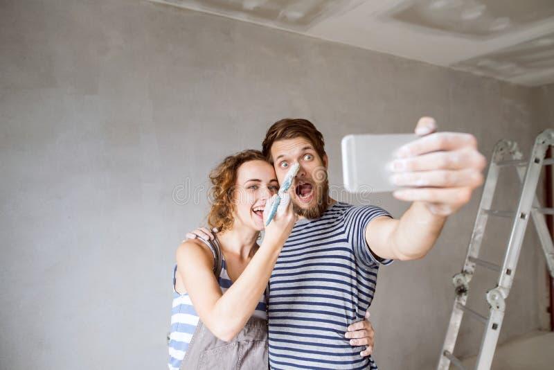 Acople em casa as paredes de pintura, tomando o selfie com smartphone fotografia de stock royalty free