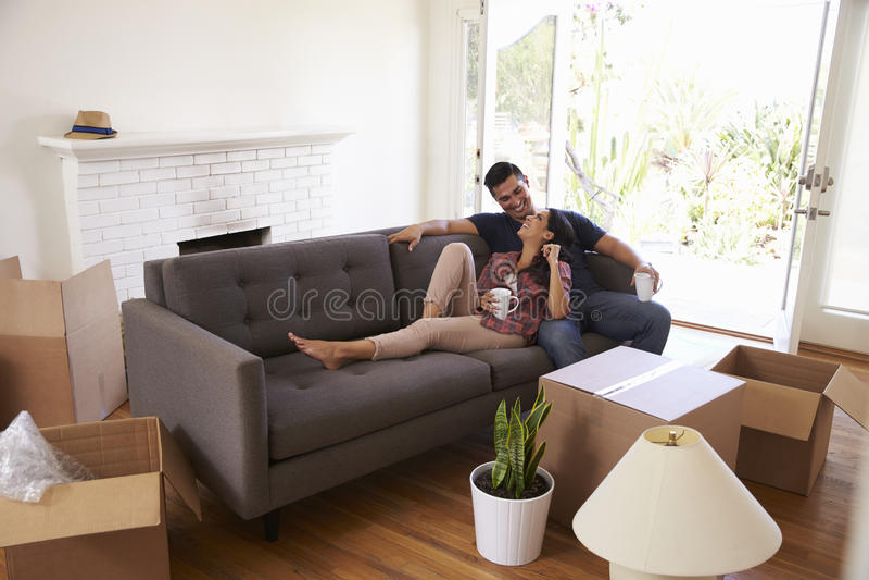 Acople em Sofa Taking uma ruptura da desembalagem em dia movente fotografia de stock