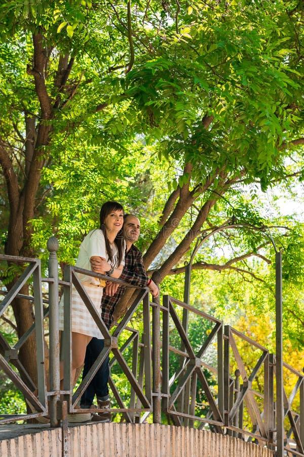 Acople em um parque, eles são sobre uma ponte imagens de stock