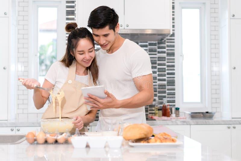 Acople a fatura da padaria na sala da cozinha, no homem asiático novo e na mulher junto imagem de stock