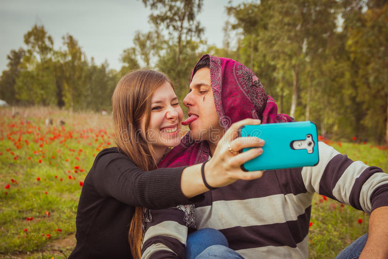 Acople fazer as caras parvas e engraçadas ao tomar a imagem w do selfie fotos de stock royalty free