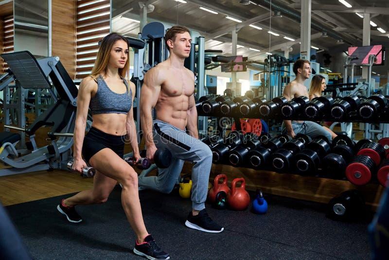 Acople fazer a ocupa sentar-UPS com pesos no gym foto de stock royalty free