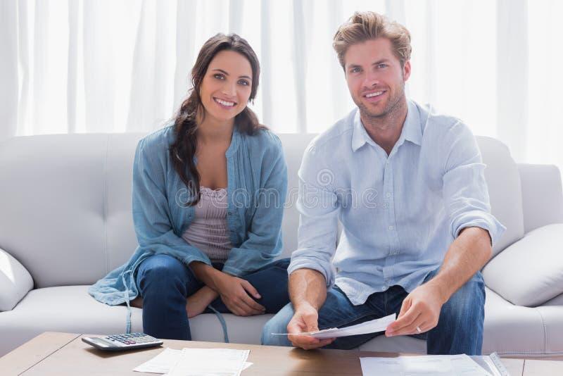 Acople fazer suas contas sentadas em um sofá imagem de stock royalty free
