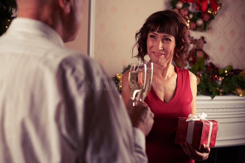 Acople flautas de champanhe do tinido na frente da decoração da chaminé imagem de stock royalty free