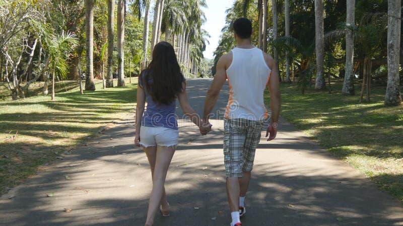 Acople guardar as mãos de se e o passeio no parque tropical Homem novo e mulher que vão ao longo do parkland exótico fotos de stock