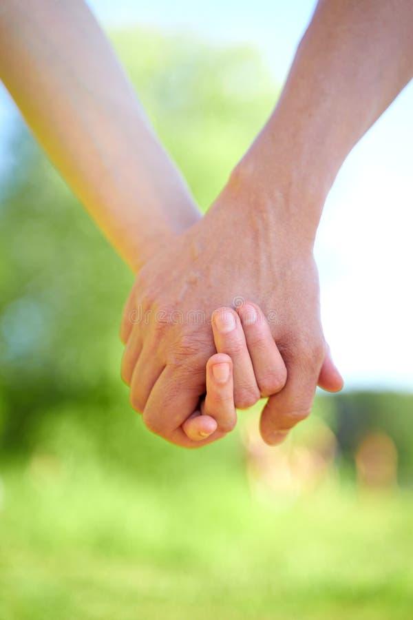Acople guardar as mãos e andar no tempo ensolarado do verão fotografia de stock