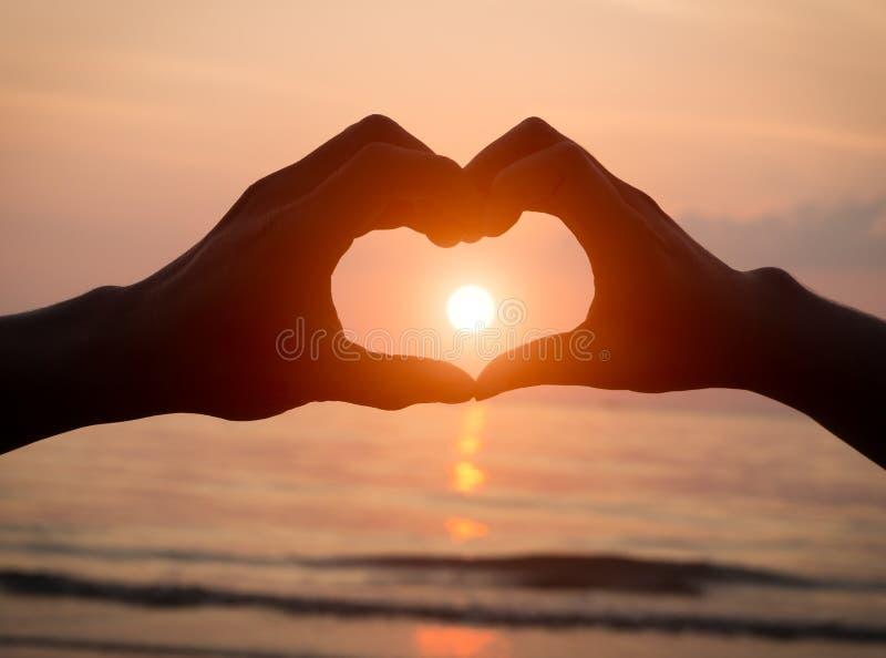 Acople guardar o amor do coração das mãos no por do sol na praia fotografia de stock