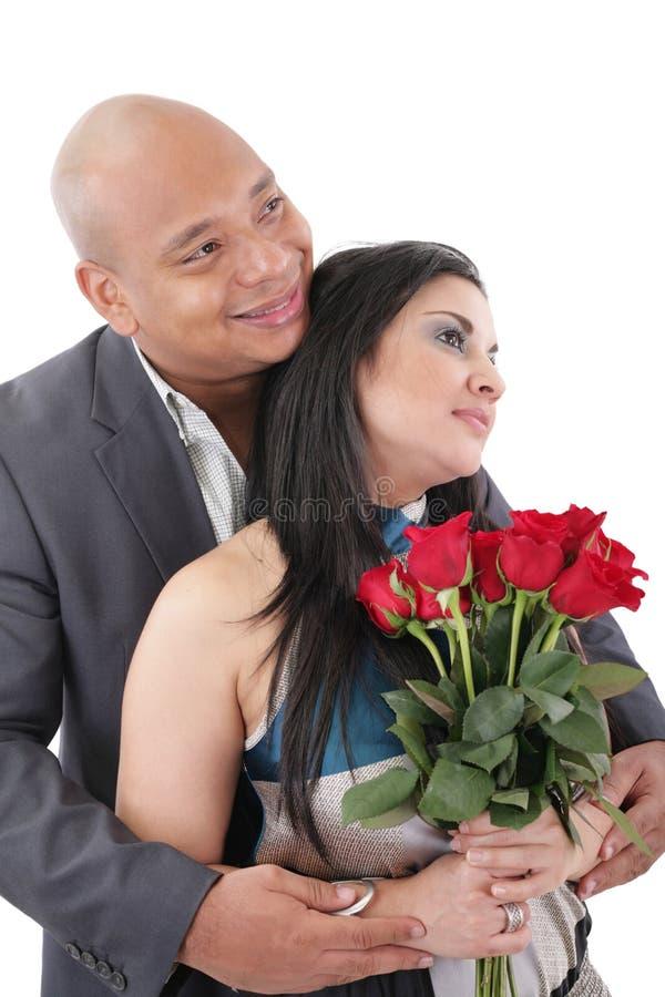 Acople guardar um ramalhete das rosas vermelhas que olham um copyspace fotografia de stock royalty free