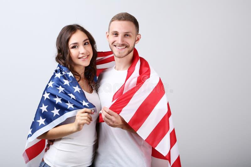 Acople guardar uma bandeira americana fotografia de stock