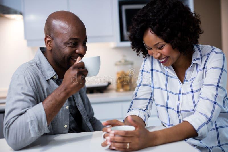Acople a interação um com o otro ao comer o café na cozinha fotografia de stock