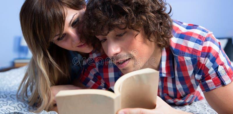 Acople a leitura de um livro na cama imagens de stock