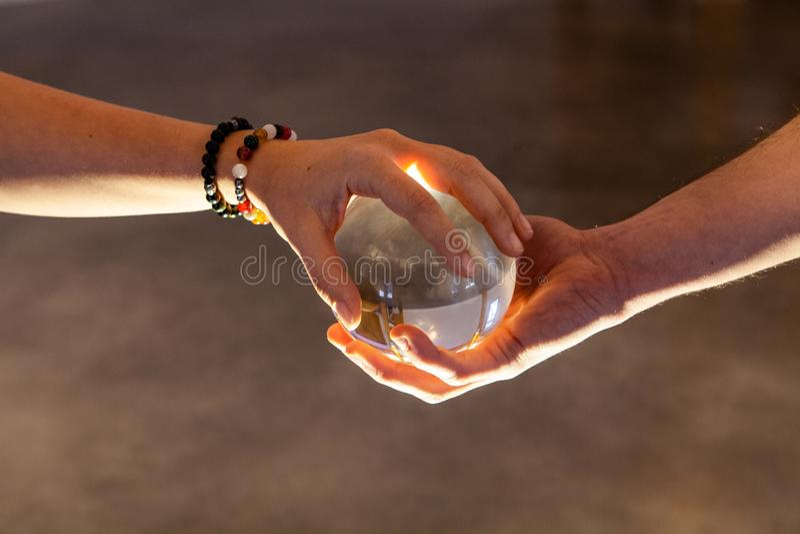 Acople manter uma bola de cristal unida imagens de stock