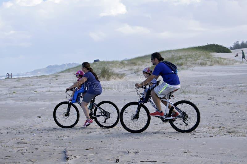 Acople a montada de uma bicicleta com suas crianças na praia de Ibiraquera, Santa Catarina Brazil - 13 de março de 2016 fotos de stock