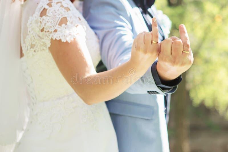 Acople mostrar os dedos médios com alianças de casamento fotos de stock royalty free