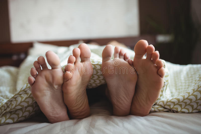 Acople mostrar seus pés ao encontrar-se em uma cama imagem de stock