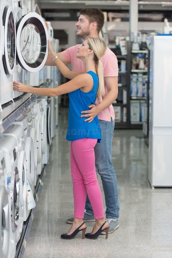 Acople na máquina de lavar da compra da loja de mantimentos fotografia de stock royalty free