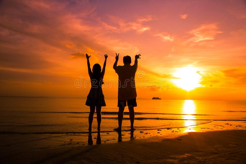 Acople na praia no ver?o silhueta-rom?ntico do por do sol fotografia de stock