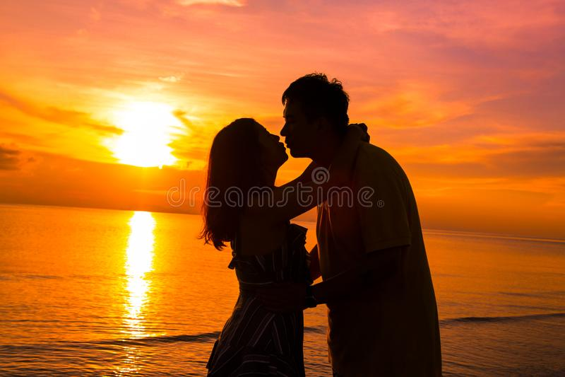 Acople na praia no ver?o silhueta-rom?ntico do por do sol imagens de stock royalty free