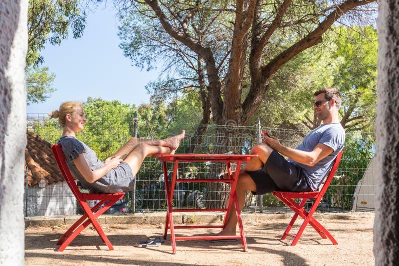 Acople nas férias que descansam na frente da casa do bungalow no local de acampamento na natureza pura Curso das férias em famíli imagens de stock royalty free