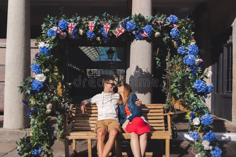 Acople no amor assentado em um banco de balanço no jardim covent Londres imagem de stock royalty free