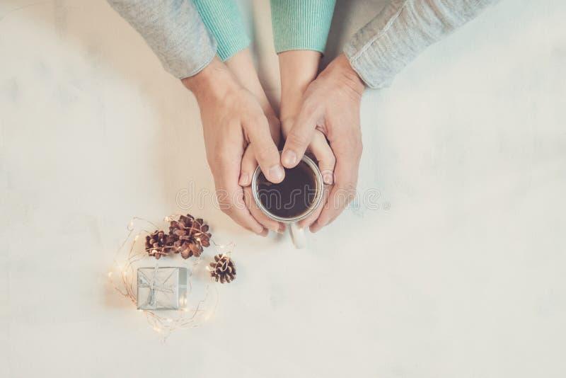 Acople no amor que guarda as mãos com café na tabela de mármore branca, com luzes de Natal Fotografia tomada de cima de, parte su fotografia de stock