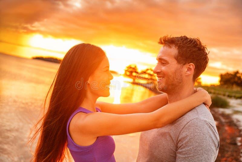 Acople no amor que ri do fulgor do por do sol em férias das caraíbas tropicais da praia do verão Mulher asiática feliz que sorri  fotografia de stock