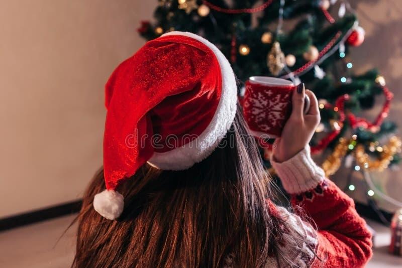 Acople no amor que senta-se ao lado de uma árvore de Natal, vestindo o chapéu de Santa e o aperto Jovens que comemoram o ano novo fotos de stock royalty free