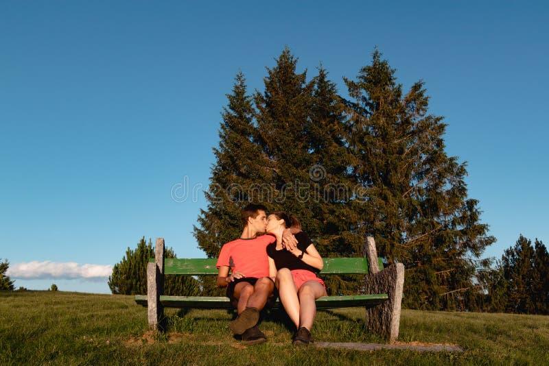 Acople no amor que senta-se no banco nas montanhas e que beija após uma caminhada imagens de stock royalty free