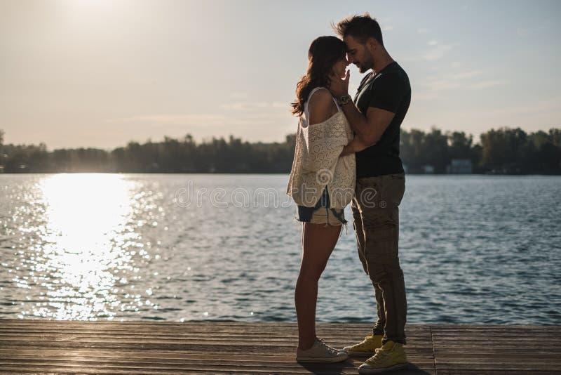 Acople no amor que toca nas cabeças pelo rio no por do sol imagem de stock royalty free