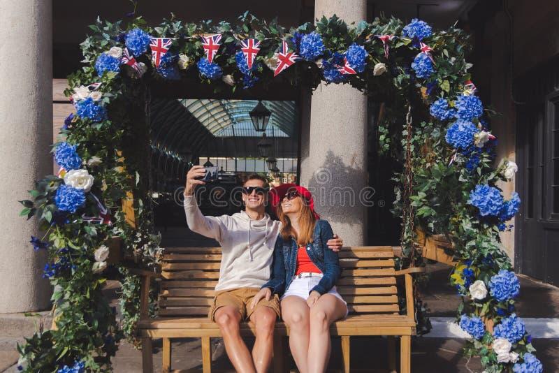 Acople no amor que toma um selfie assentado em um banco de balanço no jardim covent Londres imagem de stock royalty free