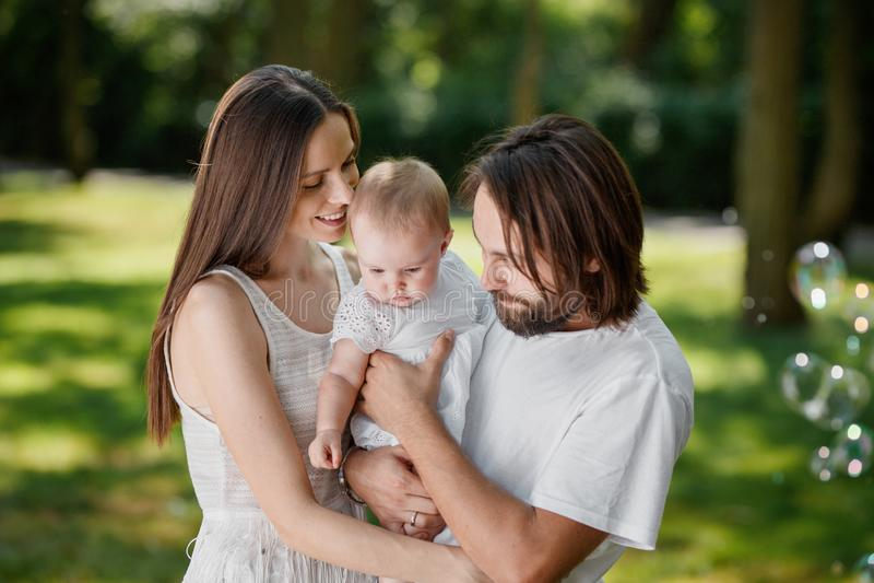 Acople no amor vestido na roupa ocasional branca está passando o tempo no parque em um dia ensolarado com o bebê lá bonito foto de stock