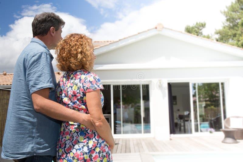 Acople o abraço na frente da casa moderna nova, vista traseira imagem de stock