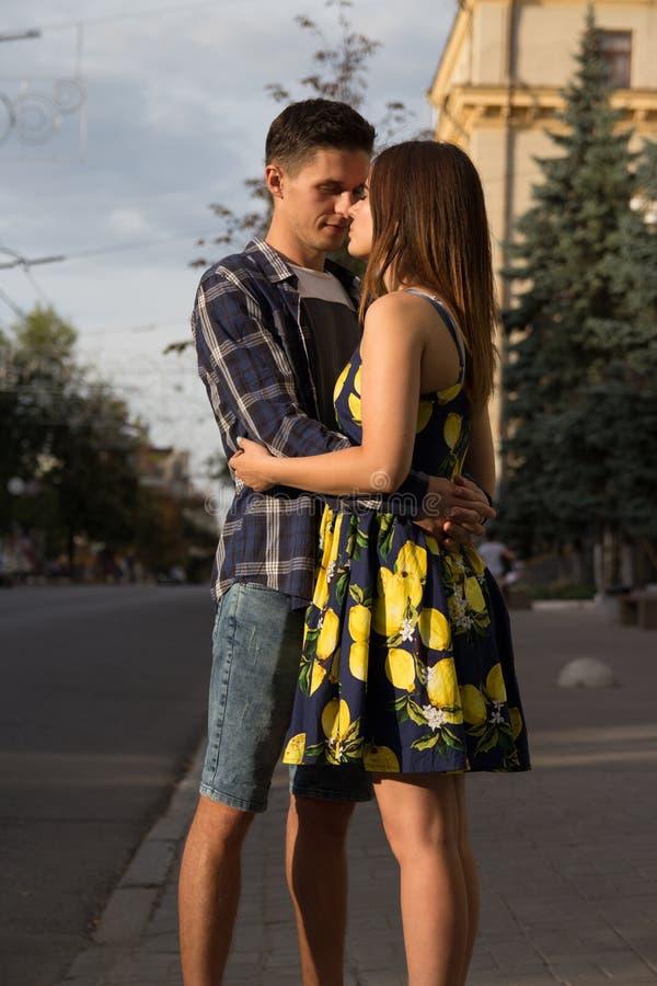 acople o abraço na perspectiva da cidade, a estrada Romance urbano o homem estica aos bordos de uma menina, quer beijá-lo foto de stock