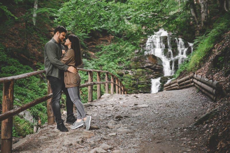 Acople o aperto e o beijo com a cachoeira no fundo imagem de stock
