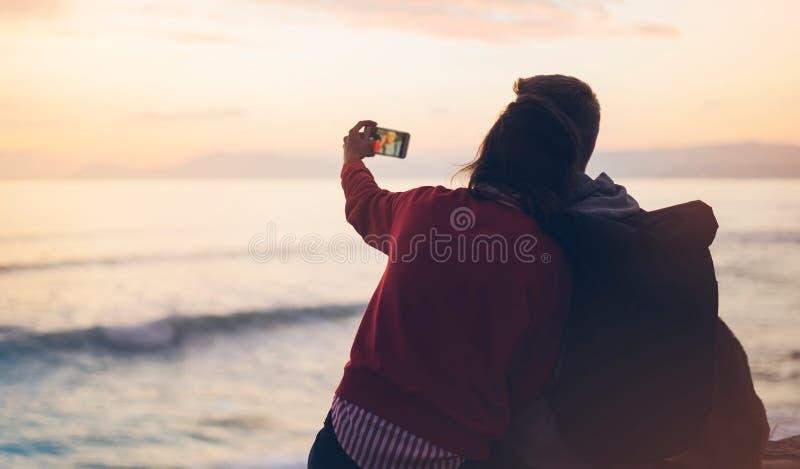 Acople o aperto no nascer do sol do oceano da praia do fundo, tome fotos no smartphone móvel, dois povos românticos que afagam e  foto de stock