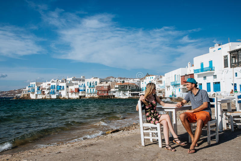 Acople o assento em cadeiras na praia, guardando as mãos fotos de stock