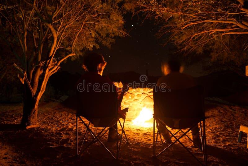 Acople o assento em fogo ardente do acampamento na noite Acampando na floresta sob o céu estrelado, Namíbia, África Aventuras do  imagem de stock royalty free