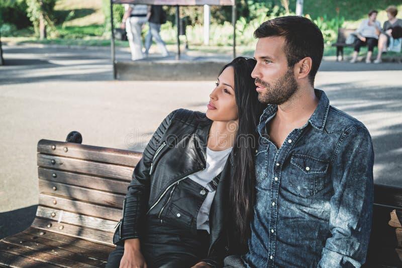 Acople o assento em um banco de parque que aprecia a vista fotografia de stock