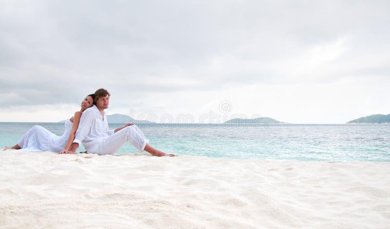 Acople o assento na praia perto do beira-mar imagem de stock