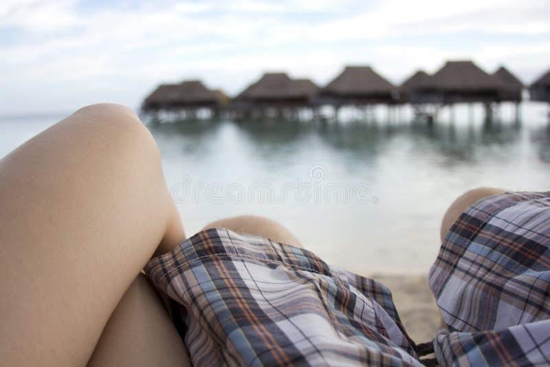 Acople o assento na rede que olha sobre as cabanas da praia e do overwater fotografia de stock royalty free