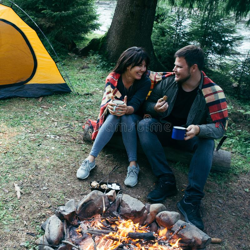 Acople o assento perto do fogo do acampamento e do chá bebendo e dizer histórias barraca e suv no fundo imagens de stock