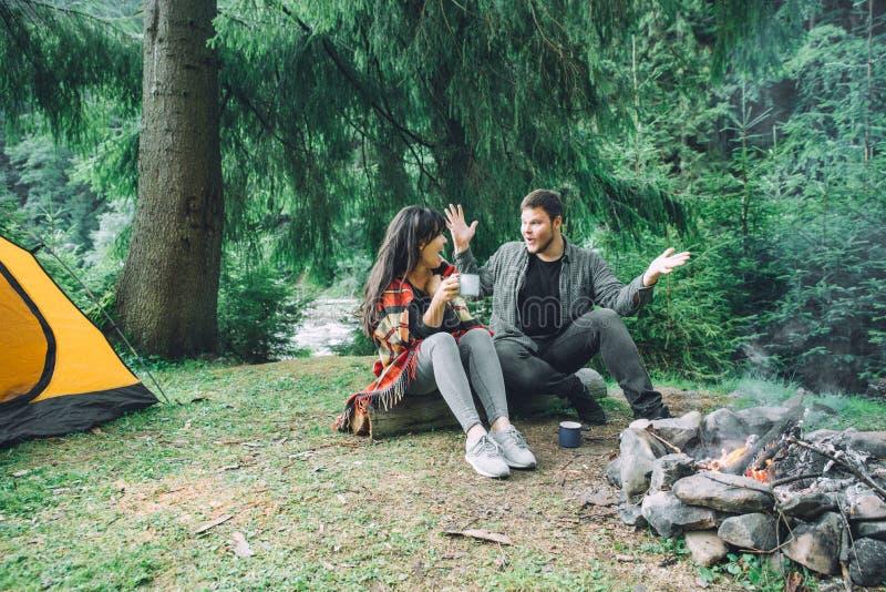 Acople o assento perto do fogo do acampamento e do chá bebendo e dizer histórias barraca e suv no fundo fotos de stock royalty free