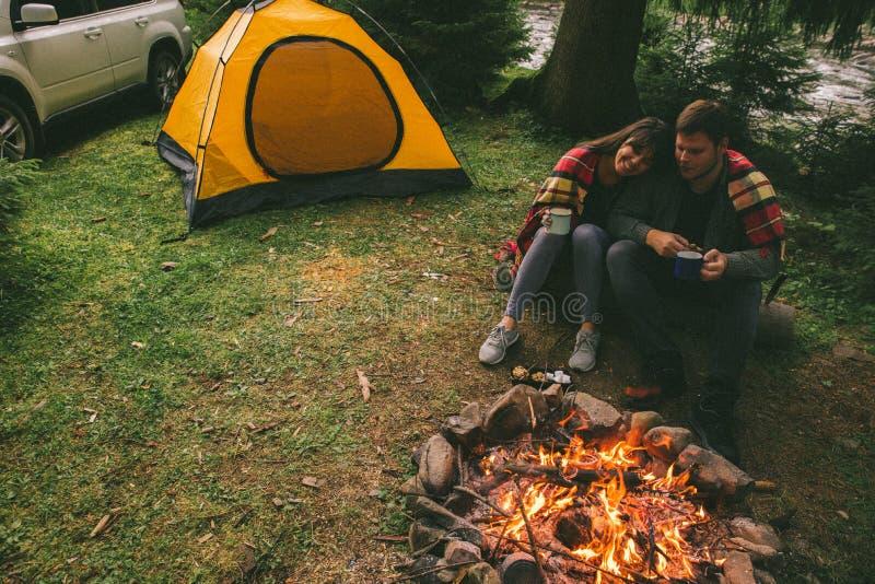 Acople o assento perto do fogo do acampamento e do chá bebendo e dizer histórias barraca e suv no fundo imagens de stock royalty free