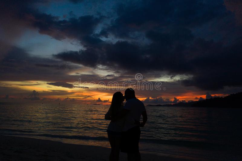 Acople o beijo na praia com um por do sol bonito no fundo fotos de stock royalty free