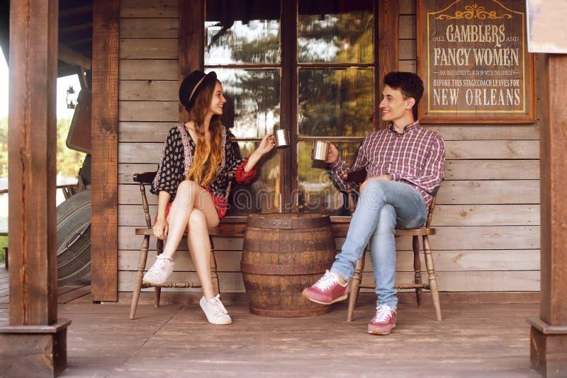 Acople o chá/café bebendo no oeste selvagem, na casa ocidental Menina no chapéu com cabelo longo Sorriso da menina e do menino, r imagem de stock