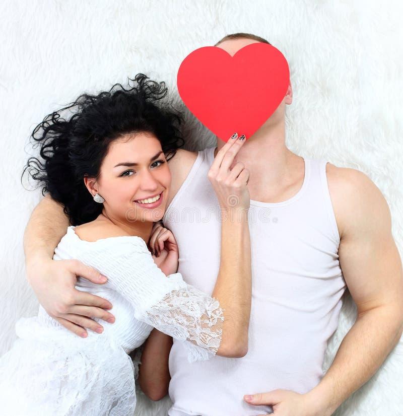 Acople o coração vermelho da terra arrendada que encontra-se junto em uma cama fotografia de stock royalty free