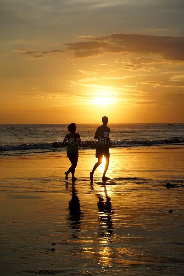 Acople o corredor na praia no por do sol em Bali imagem de stock