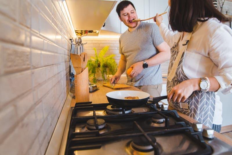 Acople o cozimento junto na cozinha fritando as panquecas que cortam a laranja Alimento do gosto foto de stock